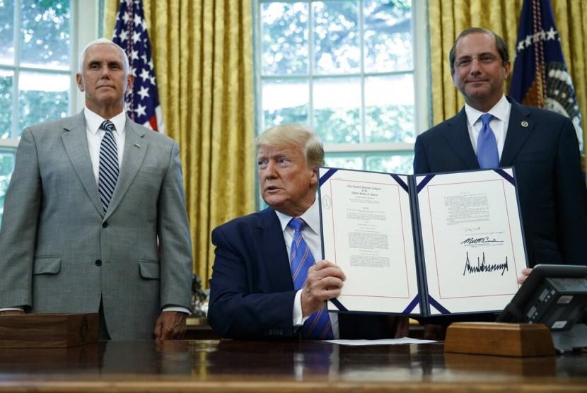 Presiden Amerika Serikat (AS) Donald Trump (tengah) menandatangani paket bantuan 4,6 miliar dolar AS untuk menangani imigran dari Amerika Tengah di perbatasan AS-Meksiko, Senin (1/7). Tampak Wakil Presiden AS Mike Pence (kiri) dan Menteri Kesehatan dan Layanan Kemanusiaan Alex Azar.