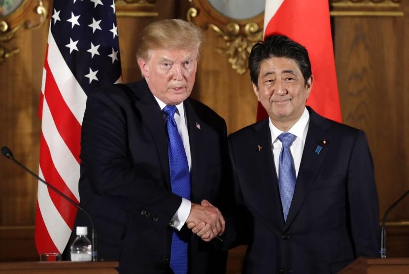 Presiden AS Donald Trump (kiri) berjabat tangan dengan Perdana Menteri Jepang Shinzo Abe di Akasaka Palace, Senin (6/11).