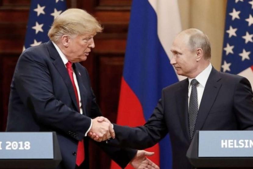 Presiden AS Donald Trump (kiri) dan Presiden Rusia Vladimir Putin (kanan) bersalaman dalam pertemuan di Helsinki, Senin (16/7).