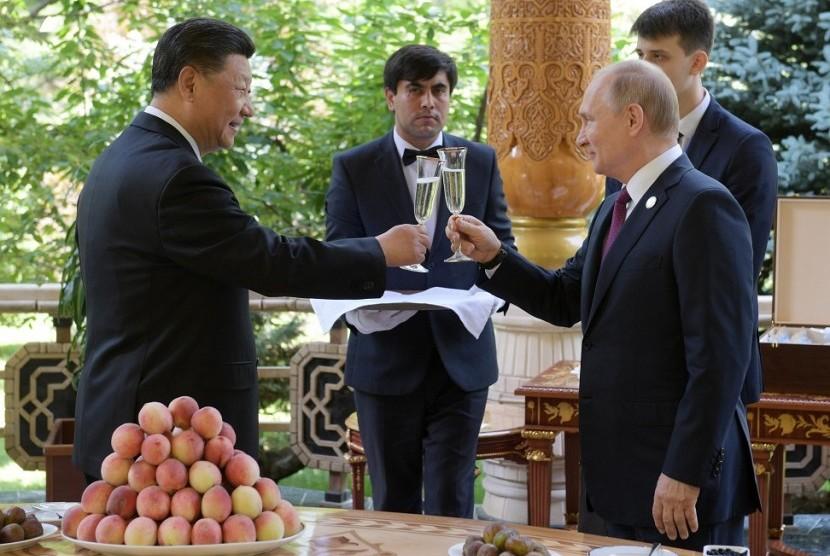Presiden China Xi Jinping (kiri) bersulang dengan Presiden Rusia Vladimir Putin.