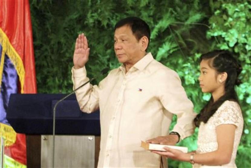 Presiden Filipina Rodrigo Duterte diambil sumpah dalam pelantikannya sebagai presiden di Istana Malacanang, Kamis, 30 Juni 2016. Putrinya Veronica tampak memegang Injil.