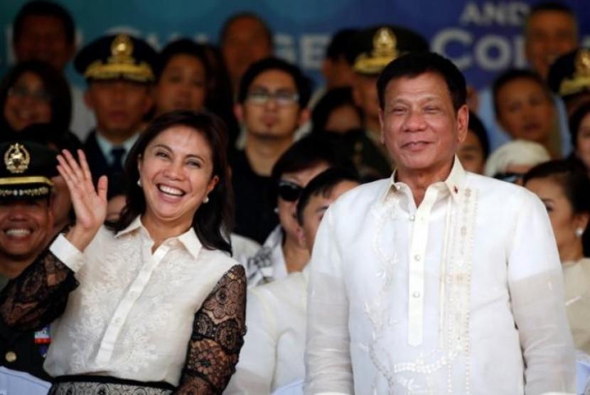 Presiden Filipina Rodrigo Duterte (kanan) bersama Wakil Presiden Leni Robredo berpose setelah parade militer di Camp Aguinaldodi Metro Manila, Filipina, 1 Juli 2016.