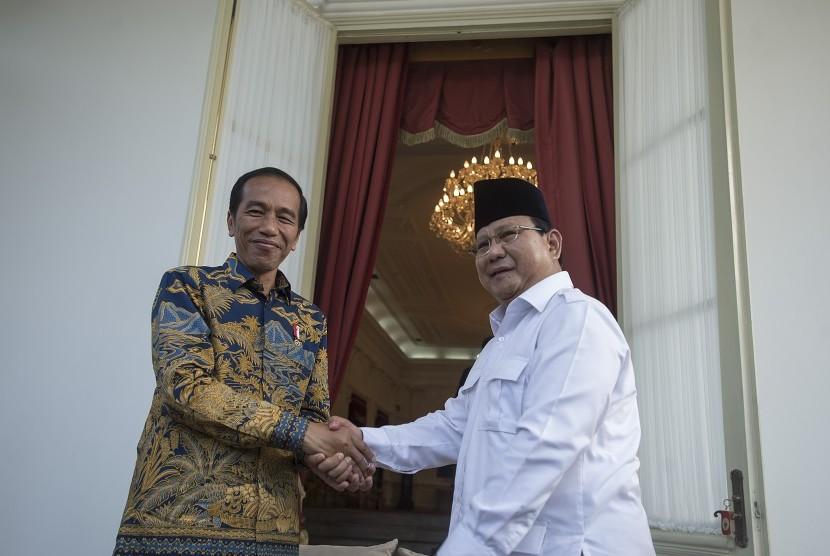 Presiden Joko Widodo berjabat tangan dengan Ketua Umum DPP Partai Gerakan Indonesia Raya Prabowo Subianto (kanan) seusai memberikan keterangan pers di teras belakang Istana Merdeka, Jakarta, Kamis (17/11).