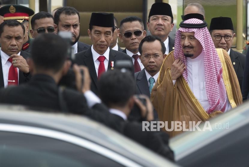 Presiden Joko Widodo berjalan bersama Raja Salman bin Abdul Aziz Al-Saud dari Arab Saudi di Bandara Halim Perdanakusuma, Jakarta, Rabu (1/3). Tampak Muchlis M Hanafi di antara keduanya bertugas sebagai penerjemah.
