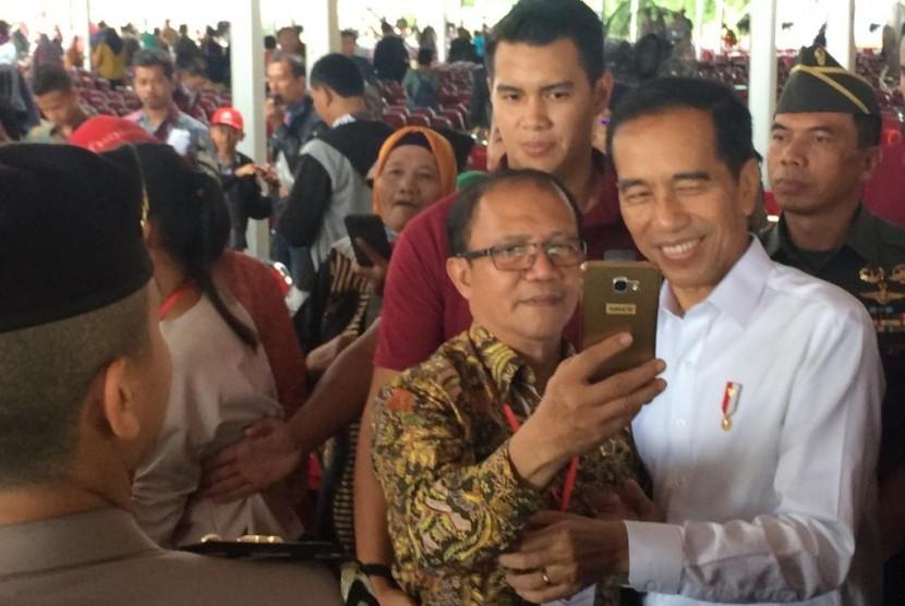 Presiden Joko Widodo berswafoto bersama warga usai menyerahkan 40.172 sertifikat tanah ke warga Kota Tangsel di Lapangan Terbang Pondok Cabe, Jumat (25/1).
