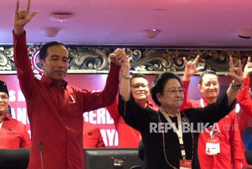 Presiden Joko Widodo dan Ketua Umum PDI Perjuangan, Megawati Soekarnoputri berfoto sembari mengangkat tiga jari usai menetapkan kembali Joko Widodo sebagai Capres 2019.