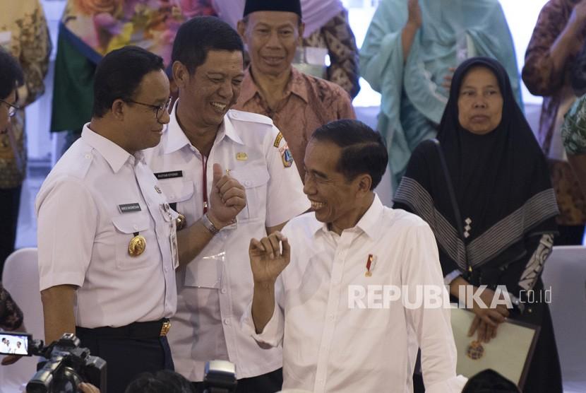 Presiden Joko Widodo (kanan) berbincang dengan Gubernur DKI Jakarta Anies Baswedan (kiri) dan Wali Kota Jakarta Barat Rustam Effendi (tengah) usai menyerahkan Sertifikat Tanah untuk Rakyat di Cengkareng, Jakarta, Rabu (9/1/2019).