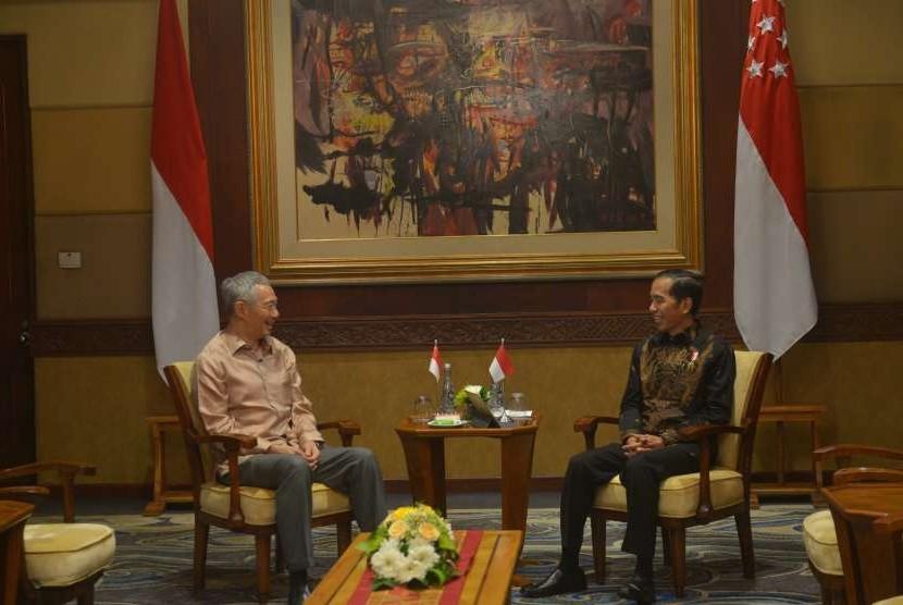 Presiden Joko Widodo (kanan) berbincang dengan Perdana Menteri Singapura Lee Hsien Loong (kiri) saat mengadakan pertemuan bilateral di sela Pertemuan Tahunan IMF - World Bank Group 2018 di Nusa Dua, Bali, Kamis (11/10).