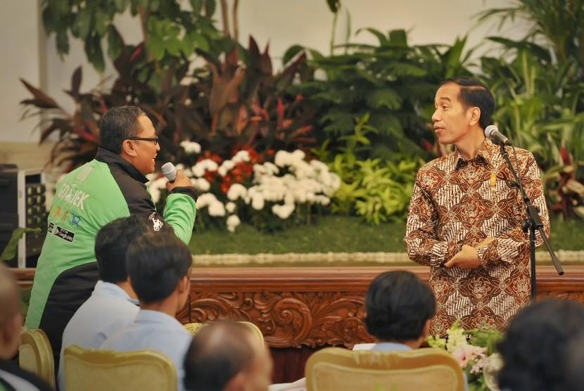 Presiden Joko Widodo (kanan) berdialog dengan pengendara ojek daring (ilustrasi).
