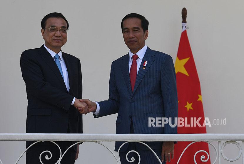 Presiden Joko Widodo (kanan) berjabat tangan dengan Perdana Menteri Cina Li Keqiang (kiri) saat kunjungan kenegaraan di beranda Istana Bogor, Jawa Barat, Senin (7/5).