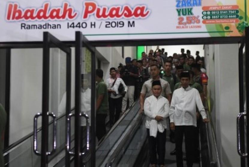Presiden Joko Widodo (kanan) bersama Gubernur Kalteng Sugianto Sabran (kiri) berjalan keluar usai menunaikan shalat tarawih di Masjid Darul Arqam, Palangka Raya, Kalimantan Tengah, Selasa (7/5/2019).