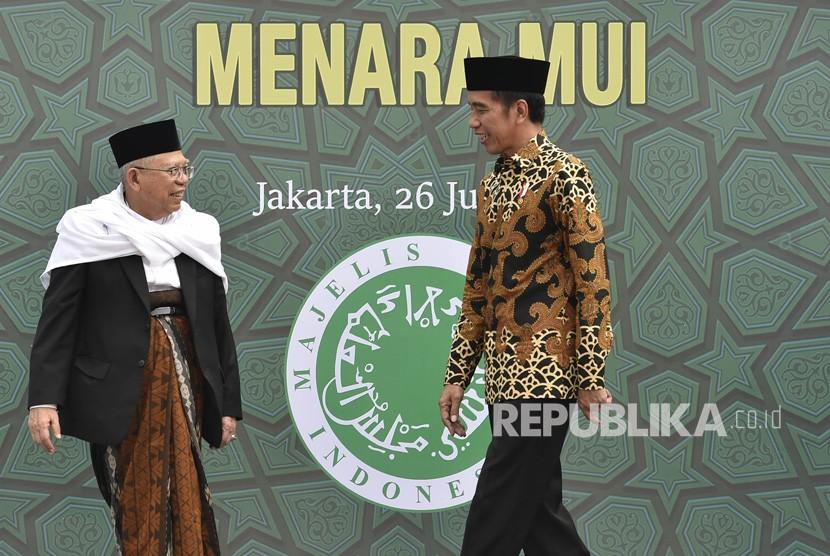 Presiden Joko Widodo (kanan) bersama Ketua Umum Majelis Ulama Indonesia (MUI) Maruf Amin menuju tempat peletakan batu pertama proyek pembangunan Menara MUI di Bambu Apus, Jakarta, Kamis (26/7).