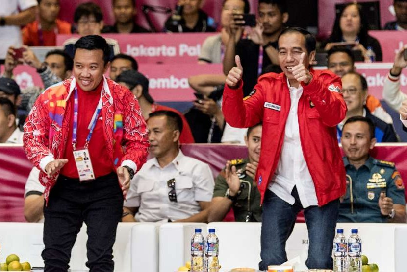 Presiden Joko Widodo (kanan) dan Menpora Imam Nahrawi (kiri) berekspresi usai menyaksikan atlet wushu putri Indonesia Lindswell berlaga dalam nomor Taijijian Putri Wushu Asian Games 2018 di JIExpo, Kemayoran, Jakarta, Senin (20/8).