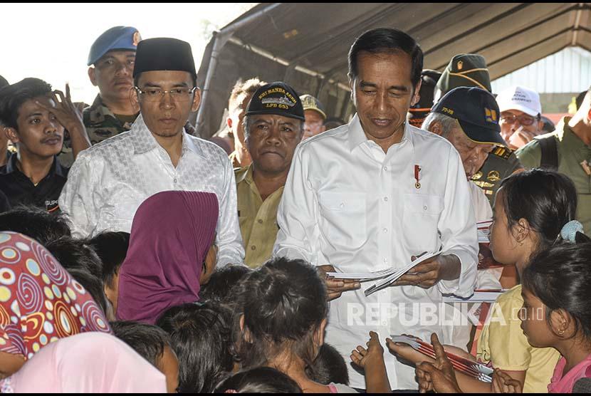Presiden Joko Widodo (kanan) didampingi Gubernur NTB TGB Zainul Majdi (kedua kiri) membagikan buku kepada anak-anak korban gempa di Desa Madayin, Kecamatan Sambelia, Selong, Lombok Timur, NTB, Senin (30/7).