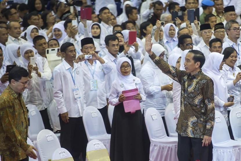 Presiden Joko Widodo (kanan) melambaikan tangan ke arah para guru yang hadir pada acara puncak Peringatan Hari Guru Nasional ke-21 Tahun 2015 di Istora Senayan, Jakarta, Selasa (24/11).