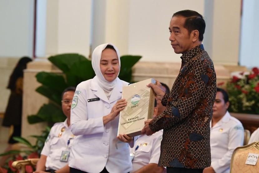 Presiden Joko Widodo (kanan) menerima katalog gempa bumi dan tsunami dari Kepala Badan Meteorologi, Klimatologi dan Geofisika (BMKG) Dwikorita Karnawati (kiri) saat membuka Rapat Koordinasi Nasional (Rakornas) BMKG tahun 2019 di Istana Negara, Jakarta, Selasa (23/7/2019).