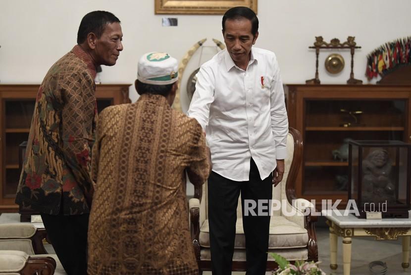 Presiden Joko Widodo (kanan) menerima pedagang kaki lima yang menjadi korban penjarahan saat aksi 22 Mei, Abdul dan Ismail di Istana Merdeka, Jakarta, Jumat (24/5/19).
