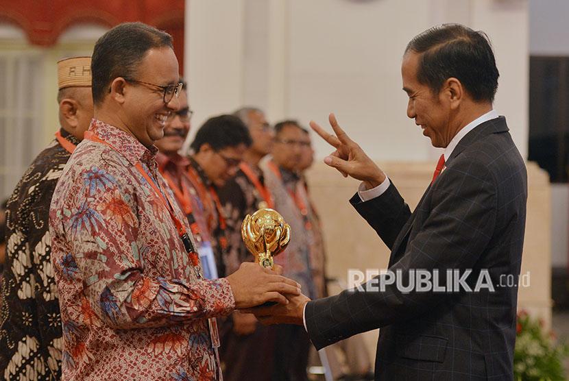 Presiden Joko Widodo (kanan) menyerahkan penghargaan Jaminan Kesehatan Nasional-Kartu Indonesia Sehat (JKN-KIS) Award kepada Gubernur DKI Jakarta Anies Baswedan ketika menerima pengguna manfaat kartu tersebut di Istana Negara, Jakarta, Rabu (23/5).