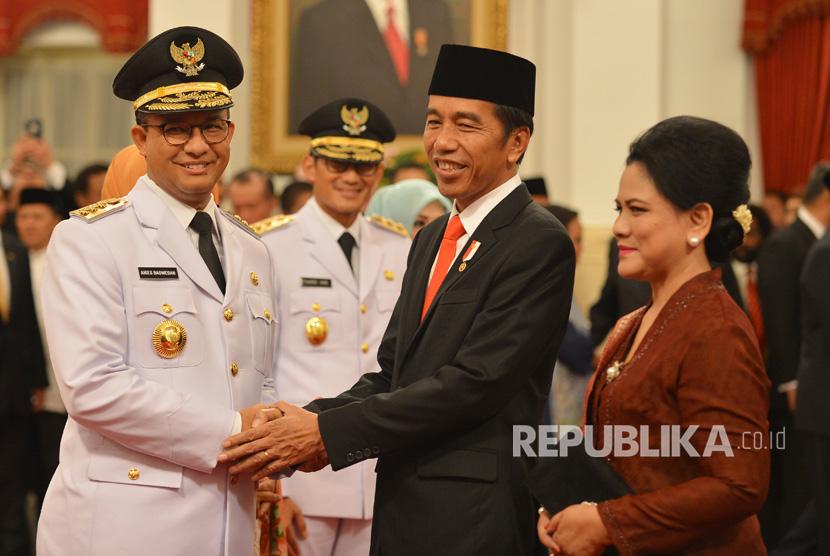 Presiden Joko Widodo (kedua kanan) didampingi Ibu Negara Iriana Joko Widodo (kanan) memberikan ucapan selamat kepada Gubernur DKI Jakarta Anies Baswedan (kiri) disaksikan Wakil Gubernur Sandiaga Uno saat pelantikan, di Istana Negara, Jakarta, Senin (16/10).