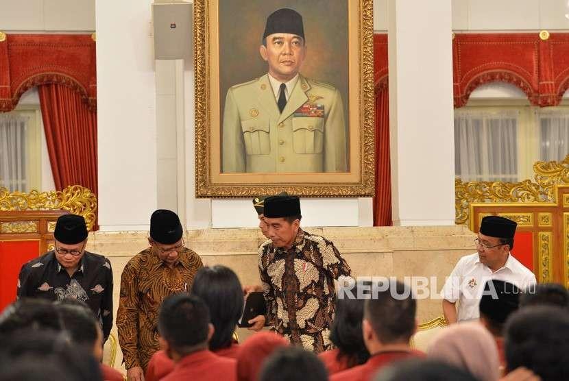 Presiden Joko Widodo (kedua kanan) didampingi Mensesneg Pratikno (kanan), Ketua Umum PP Muhammadiyah Haedar Nashir (kedua kiri) dan Ketua PP Muhammadiyah Hajriyanto Y Tohari (kiri) bersiap memberikan sambutan ketika menutup Muktamar Ikatan Mahasiswa Muhammadiyah (IMM) di Istana Negara, Jakarta, Senin (6/8).