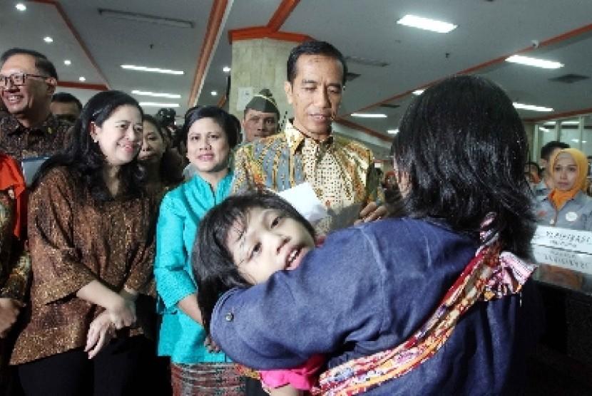 Presiden Joko Widodo (kedua kanan) memberi Kartu Indonesia Sehat (KIS), Kartu Indonesia Pintar (KIP) dan Kartu Keluarga Sejahtera (KKS).