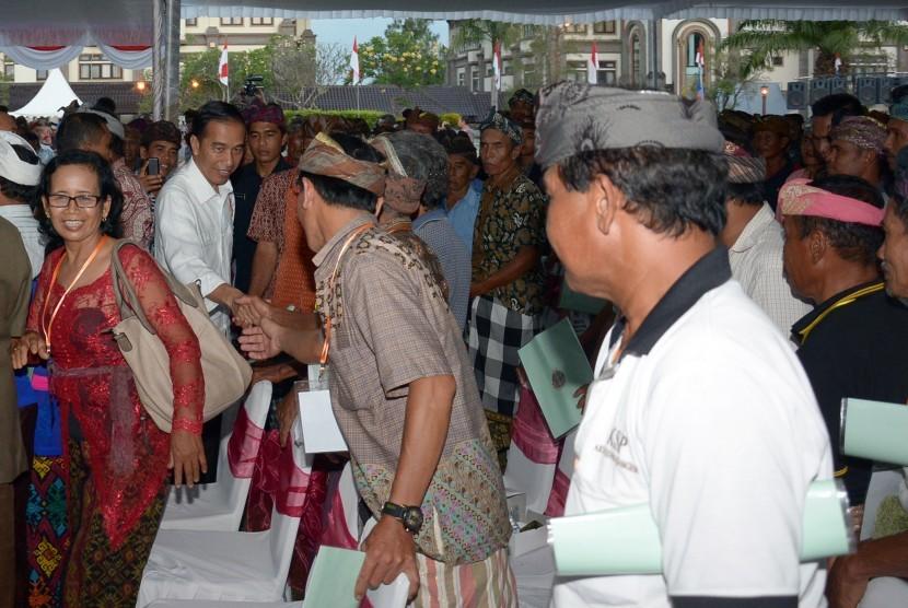 Presiden Joko Widodo (kedua kiri) berjabat tangan dengan warga saat penyerahan sertifikat tanah kepada warga di Mangupura, Kabupaten Badung, Bali, Jumat (8/9).
