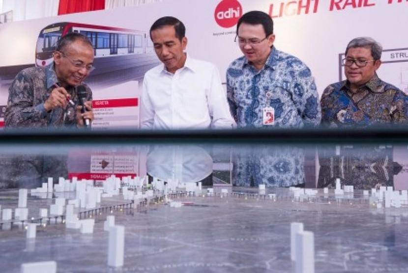 Presiden Joko Widodo (kedua kiri) didampingi Gubernur DKI Jakarta Basuki Tjahaja Purnama (kedua kanan) dan Gubernur Jawa Barat Ahmad Heryawan (kanan) mendengarkan penjelasan maket proyek pembangunan Light Rail Transit (LRT) dari Direktur Utama Adhi Karya K
