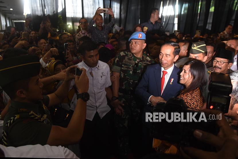 Presiden Joko WIdodo (ketiga kanan) menyapa para pelaku UMKM seuasai peluncuran aturan penurunan tarif Pajak Penghasilan Final 0,5 persen bagi UMKM di Surabaya, Jawa Timur, Jumat (22/6).