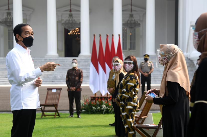 Presiden Joko Widodo (kiri) berbincang dengan sejumlah pelaku usaha saat penyerahan Bantuan Presiden Produktif Usaha Mikro (BPUM) di Halaman Istana Merdeka, Jakarta, Jumat (30/7/2021). Presiden Joko Widodo menyerahkan BPUM sebesar Rp15,3 triliun kepada 12,8 juta pelaku usaha mikro dan kecil di seluruh Indonesia yang belum pernah menerima sebelumnya.