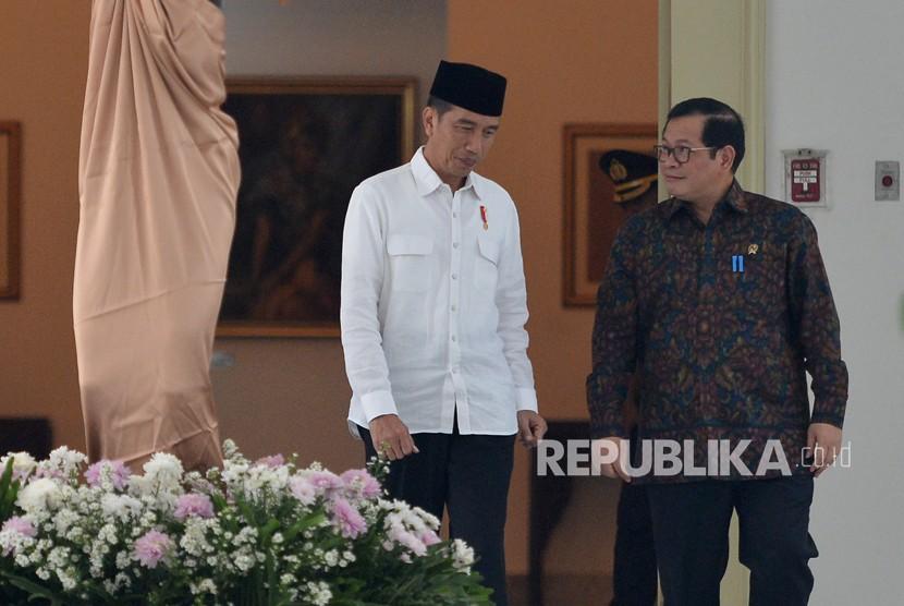 Presiden Joko Widodo (kiri) berbincang dengan Seskab Pramono Anung sebelum memimpin rapat kerja persiapan Asian Games XVIII di Istana Bogor, Jawa Barat, Rabu (18/4).