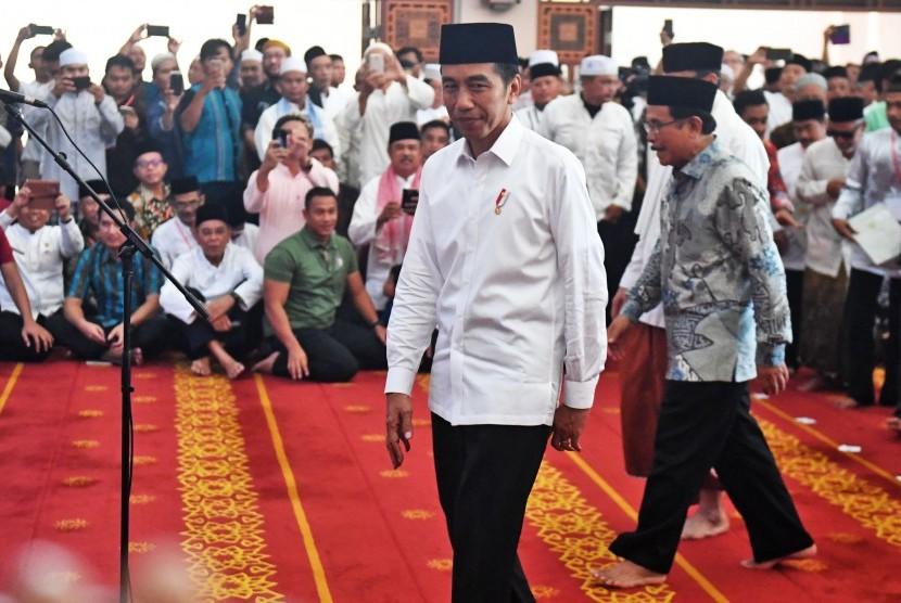 Jokowi Bagi Sertifikat Wakaf: Presiden Joko Widodo (kiri) berjalan usai memberikan sertifikat tanah wakaf kepada warga di Masjid Raya Bani Umar, Tangerang Selatan, Jumat (22/2/2019).