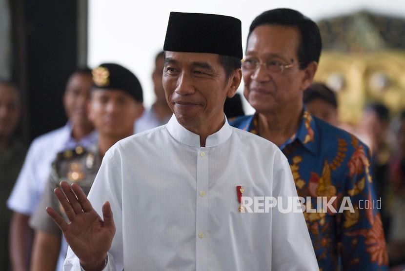 Presiden Joko Widodo (kiri) didampingi Gubernur DI Yogyakarta Sri Sultan HB X melambaikan tangan seusai melakukan pertemuan di Keraton Yogyakarta, Kamis (6/12/2018).
