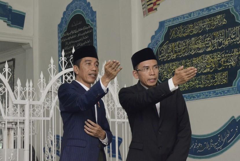 Presiden Joko Widodo (kiri) didampingi Gubernur NTB, TGB Zainul Majdi (kanan), berziarah di makam Pahlawan Nasional Maulana Syekh TGKH Muhammad Zainuddin Abdul Majid di Ponpes NW Pancor, Lombok Timur, NTB, Kamis (23/11).