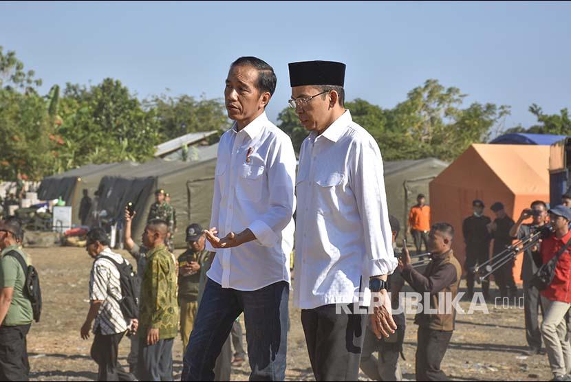 Presiden Joko Widodo (kiri) didampingi Gubernur NTB TGB Zainul Majdi (kanan) mengunjungi pengungsian korban gempa bumi di Desa Madayin, Kecamatan Sambelia, Selong, Lombok Timur, NTB, Senin (30/7). Presiden Jokowi mengatakan pemerintah akan memberikan bantuan untuk perbaikan Rp 50 juta per rumah korban gempa yang mengalami kerusakan.