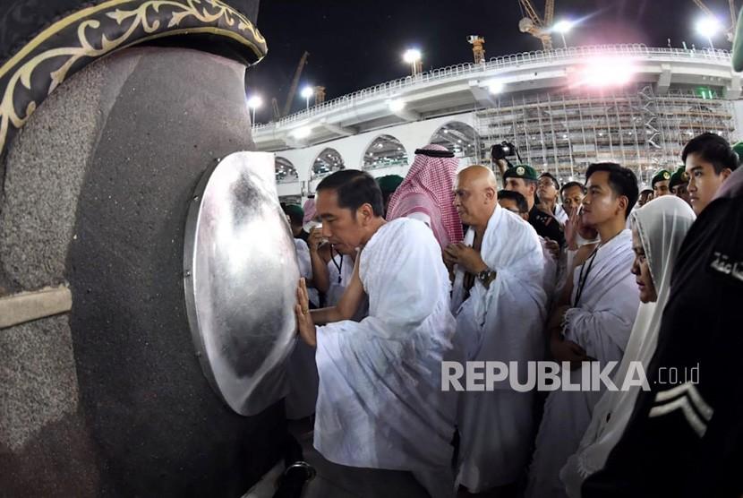 Presiden Joko Widodo (kiri) mencium Hajar Aswad saat menjalankan ibadah umrah di Masjidil Haram, Makkah, Arab Saudi, Senin (15/4/2019).
