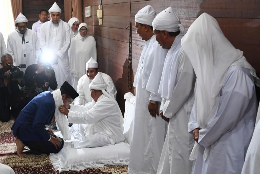 Presiden Joko Widodo (kiri) menerima sorban dari pengasuh Ponpes Babussalam Syekh Haji Hasyim Al-Syarwani Tuan Guru Babussalam di Langkat, Sumatra Utara, Sabtu (29/12/2018).