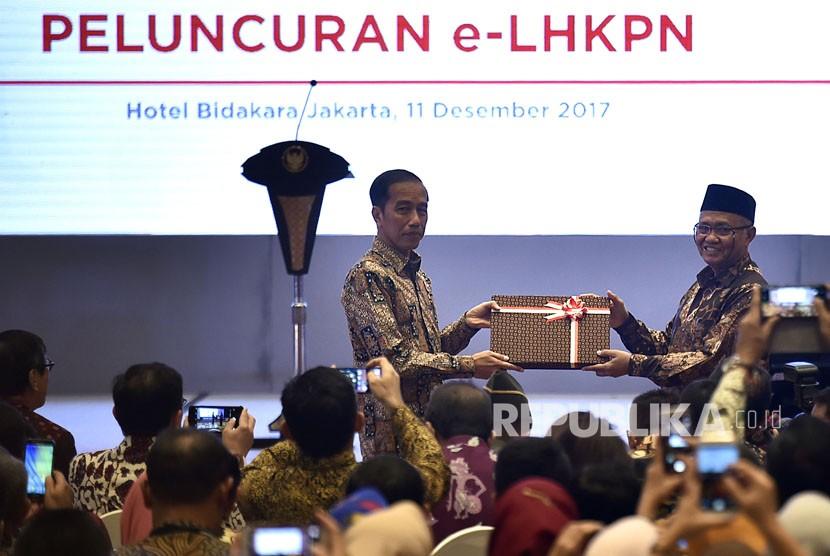 Presiden Joko Widodo (kiri) menerima user name dan password e-LHKPN dari Ketua KPK Agus Rahardjo di sela-sela Pembukaan Konferensi Nasional Pemberantasan Korupsi ke-12, sekaligus Peringatan Hari Anti Korupsi Sedunia Tahun 2017 serta Peluncuran Aplikasi e-LHKPN, di Jakarta, Senin (11/12).