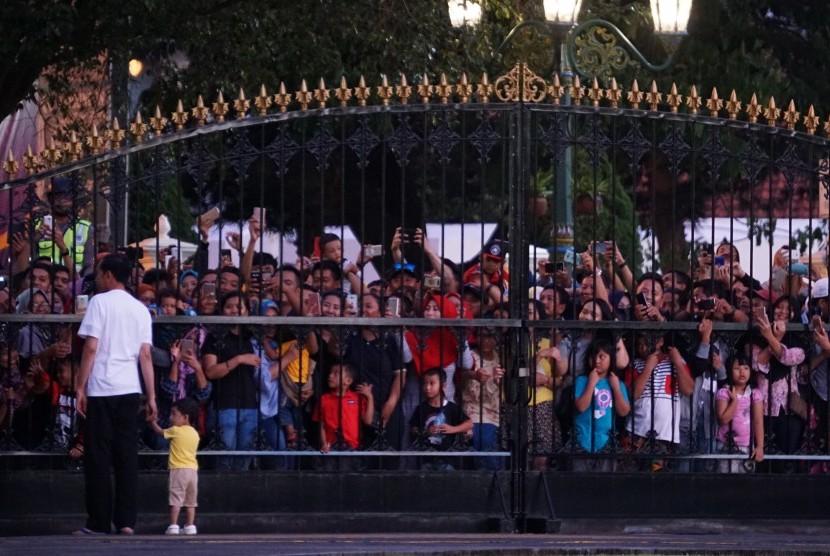 Presiden Joko Widodo (kiri) mengasuh cucunya, Jan Ethes Sri Narendra sambil menyapa warga di depan gerbang Istana Kepresidenan Yogyakarta pada Minggu sore (31/12). Presiden menunggu momen pergantian tahun dengan mengajak warga masuk ke istana dan menikmati kuliner tradisional.