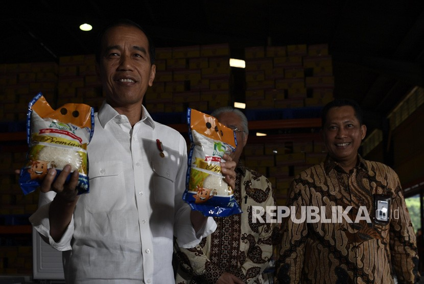 Presiden Joko Widodo (kirii) bersama Kepala Bulog Budi Waseso (kiri) menunjukkan beras kemasarn Bulog saat mengecek stok beras di Kompleks Pergudangan Bulog, Jakarta, Kamis (10/1/2019).