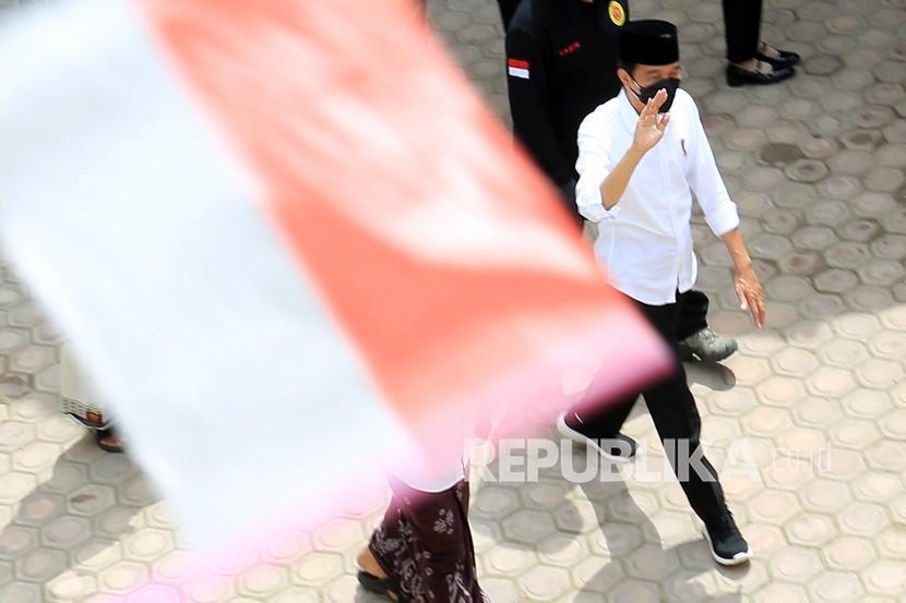 Presiden Joko Widodo melambaikan tangan kepada santri saat meninjau vaksinasi COVID-19 di Pesantren Istiqamatuddin Darul Muarif Desa Lambro Bileu, Kuta Baro, Aceh Besar, Aceh, Kamis (16/9/2021). Dalam kunjungan tersebut Presiden Joko Widodo menyaksikan secara langsung pelaksanaan vaksinasi yang dilakukan secara jemput bola atau dari rumah ke rumah sehingga dapat mempercepat vaksinasi COVID-19.