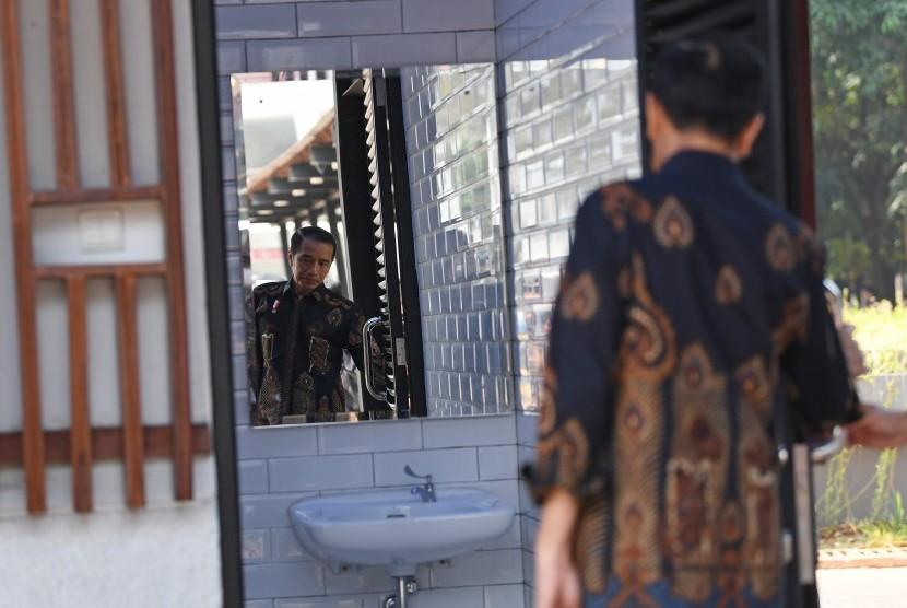 Presiden Joko Widodo mengamati toilet khusus disabilitas ketika meninjau fasilitas umum untuk masyarakat berkebutuhan khusus di Kompleks Gelora Bung Karno, Senayan, Jakarta, Selasa (16/10/2018).