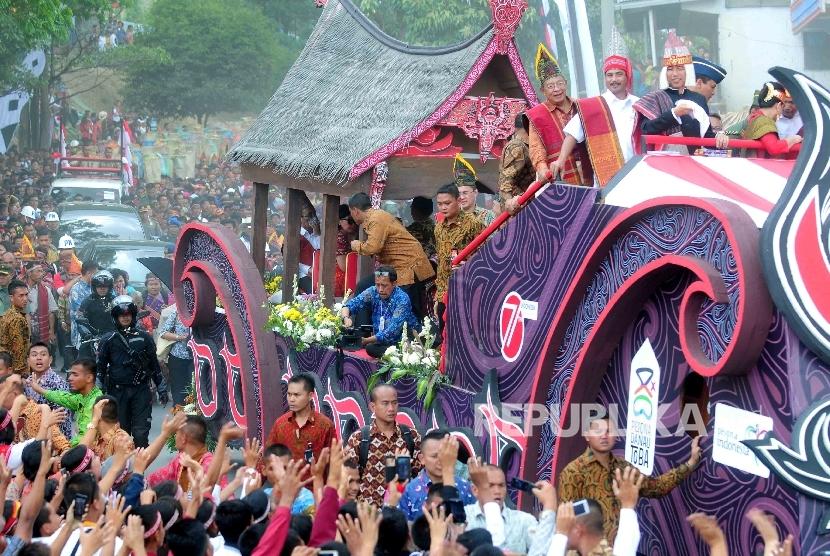 Presiden Joko Widodo mengenakan pakaian Adat Batak bersamaMenteri Pariwisata Arief Yahya menyapa warga Balige saat Karnaval Kemerdekaan Pesona Danau Toba, Balige, Sumatra Utara, Ahad (22/8).  (Republika/ Agung Supriyanto)
