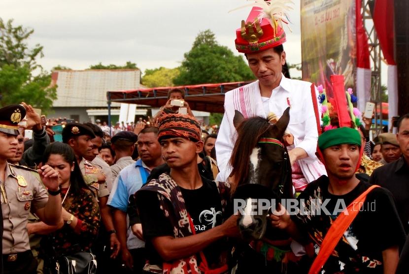 Presiden Joko Widodo menunggang kuda Sandelwood yang diberikan masyarakat Sumba Saat mengunjungi Pulau Sumba di Kota Waetabula, Kabupaten Sumba Barat Daya, NTT, Rabu (12/7).