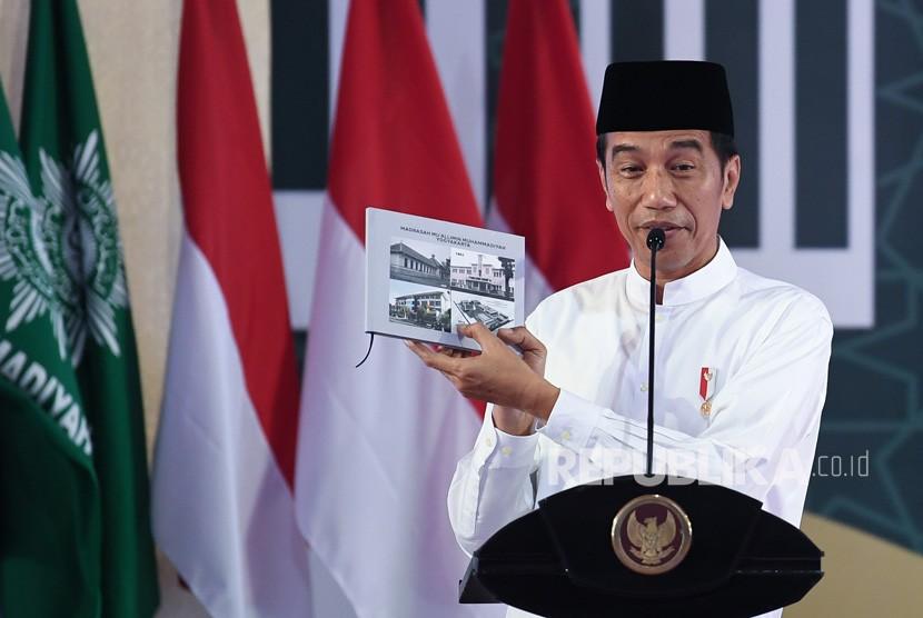 Presiden Joko Widodo menunjukkan buku ketika menghadiri milad satu abad Madrasah Muallimin dan Muallimat Muhammadiyah Yogyakarta di Yogyakarta, Kamis (6/12/2018).