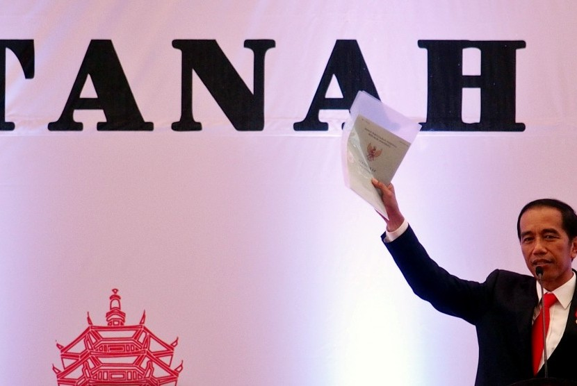 Presiden Joko Widodo menunjukkan dokumen sertifikat tanah saat berbicara pada acara penyerahan sertifikat tanah untuk rakyat, di Semarang, Jawa Tengah, Senin (9/10).