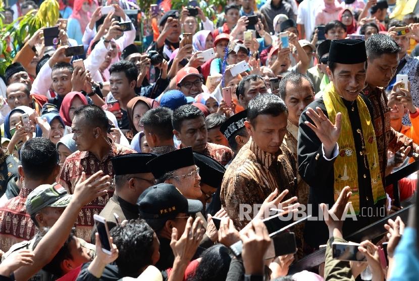 Presiden Joko Widodo menyalami warga saat menghadiri Lebaran Betawi di Kampung Budaya Betawi Setu Babakan, Jakarta, Ahad (30/7).