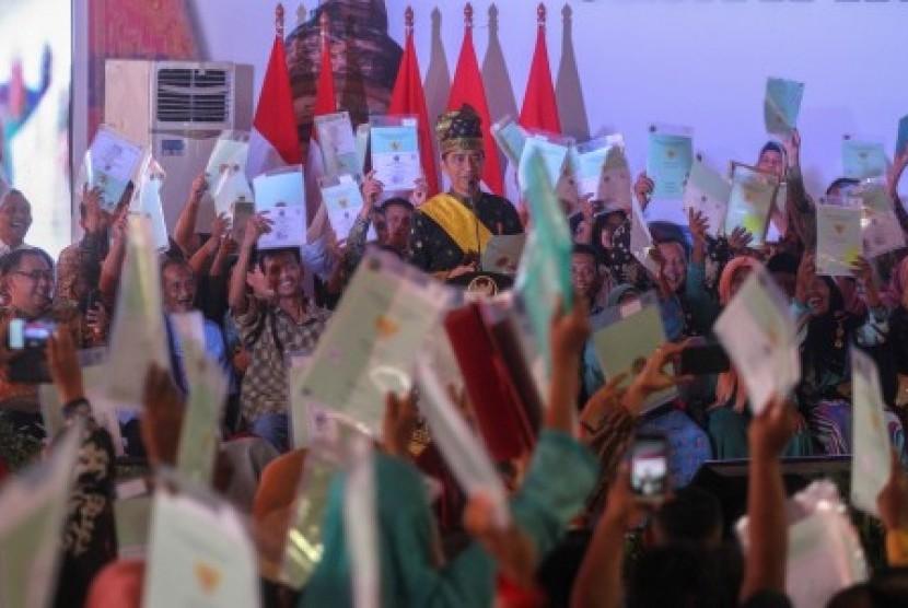 Presiden Joko Widodo menyerahkan sertifikat tanah untuk rakyat di Kota Pekanbaru, Riau, Sabtu (15/12/2018). Pada tahun 2018 ini Pemerintah akan menerbitkan sebanyak 155.000 sertifikat tanah baru dan telah diserahkan sertifikat hak atas tanah kepada 132.993 warga di Provinsi Riau.