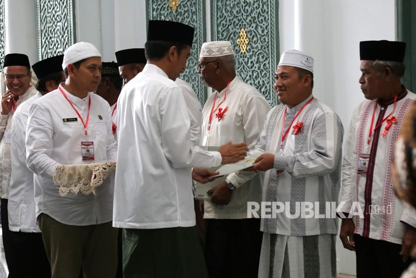 Presiden Joko Widodo menyerahkan sertifikat tanah wakaf kepada pengurus masjid, mushola dan pasantren seusai melaksanakan ibadah Jumat di Banda Aceh, Aceh, Jumat (14/12/2018).