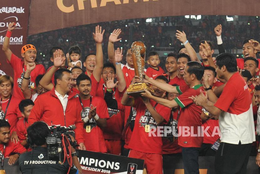 Presiden Joko Widodo menyerahkan trophy juara kepada pemain Persija Jakarta seusai menjadi juara Piala Presiden 2018 di di Gelora Bung Karno Senayan, Jakarta, Sabtu (17/2). Persija keluar sebagai juara setelah mengalahkan Bali United dengan skor 3-0.