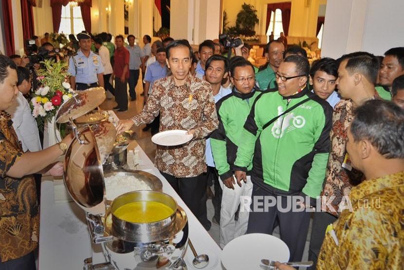 Presiden Joko Widodo (tengah) berdialog dengan pengendara Gojek saat pertemuan makan siang bersama pengemudi kendaraan umum di Istana Negara, Jakarta, Selasa (2/9).
